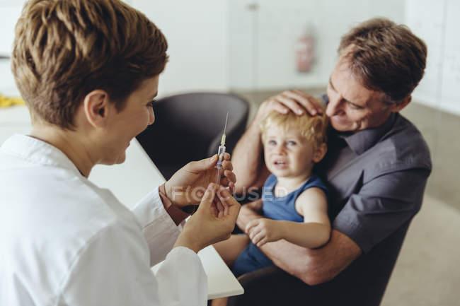 Батько тримає сина під час вакцинації педеатром. — стокове фото