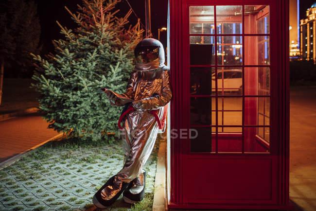 Spaceman apoyado contra la cabina telefónica por la noche y usando el teléfono - foto de stock