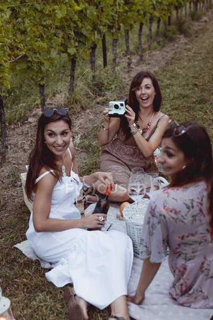Одна жінка фотографує пікнік у винограднику і вмить фотографує його. — стокове фото