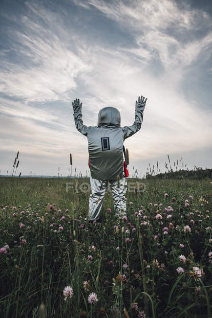 Spaceman standing in meadow with hands up — Stock Photo