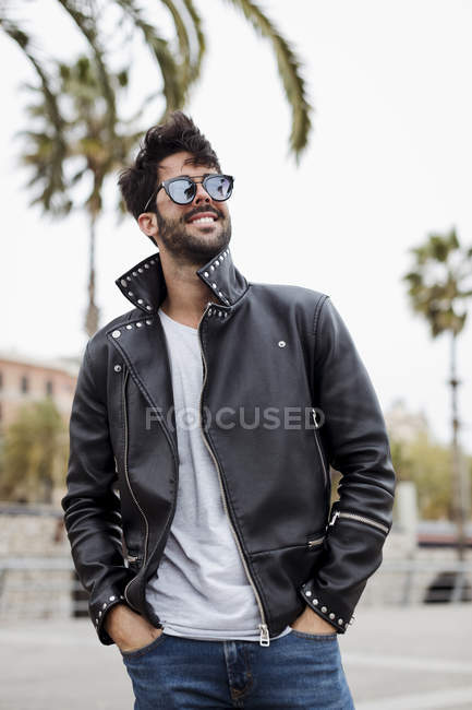 Happy young man walking on promenade with palms — Stock Photo