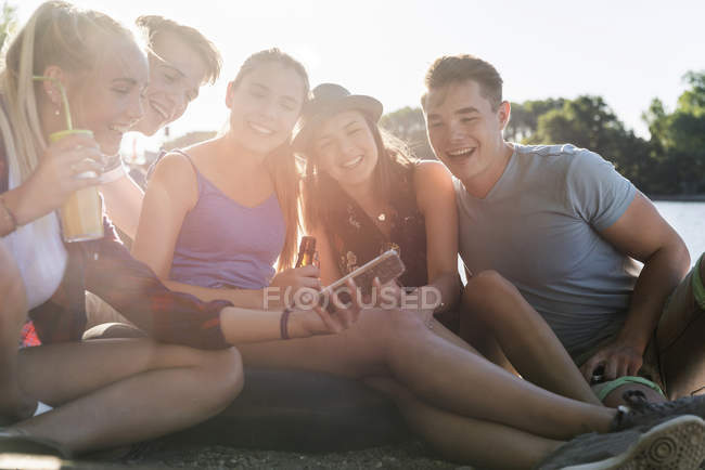 Group of happy friends sitting outdoors with drinks and cell phone — Stock Photo