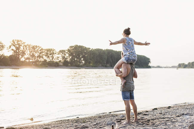 Young man giving girlfriend piggyback ride at riverbank — стокове фото