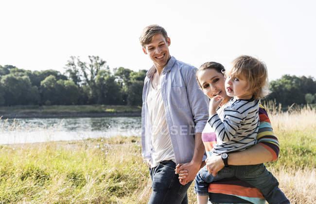 Família feliz andando na beira do rio no dia ensolarado de verão — Fotografia de Stock
