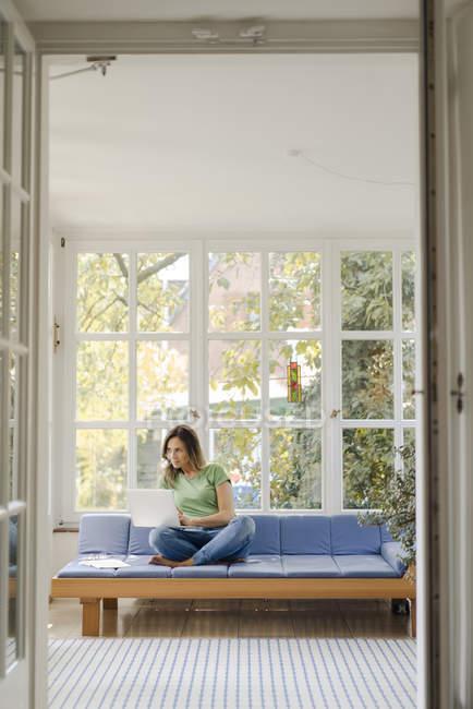 Sorridente donna matura seduta sul divano a casa con computer portatile — Foto stock