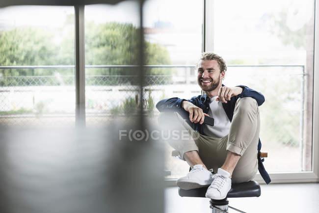 Homme d'affaires décontracté souriant assis sur une chaise de bureau avec téléphone portable — Photo de stock