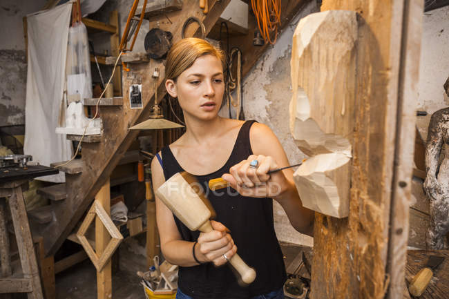 Скульптриса вырезает деревянную фигуру — стоковое фото