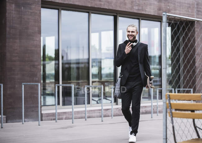 Smiling fashionable young man holding cell phone and skateboard passing office building — Stock Photo