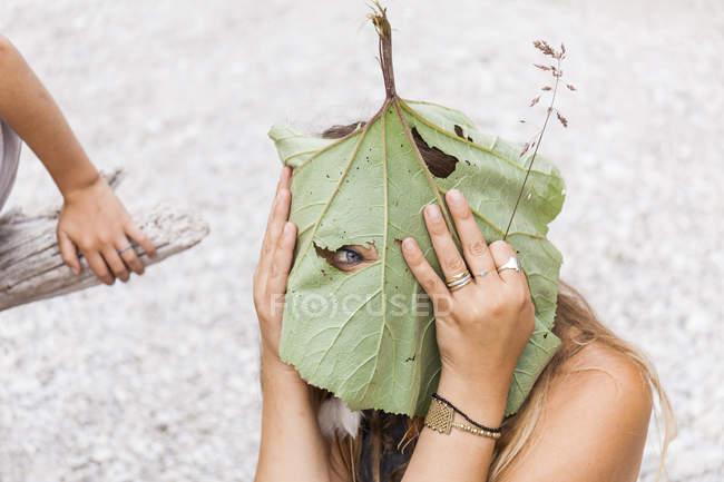 Playful woman peeking through hole in large leaf — стокове фото