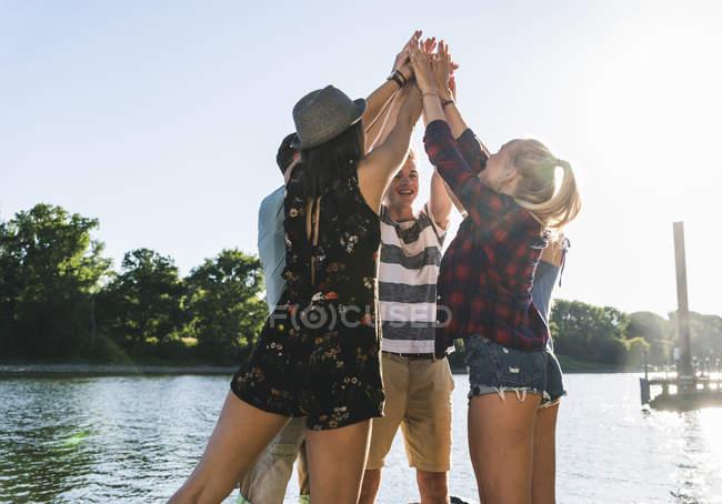Grupo de amigos que põr suas mãos junto no beira-rio — Fotografia de Stock