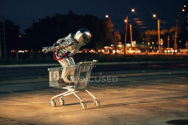 Космонавт в городе ночью на парковке, стоящей внутри тележки — стоковое фото