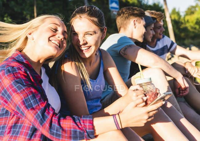 Grupo de amigos felizes sentados ao ar livre com bebidas refrescantes e telefones celulares — Fotografia de Stock