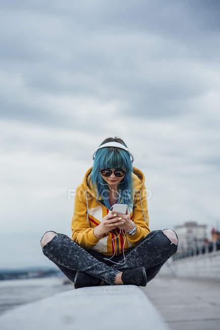 Молода жінка з фарбованим синім волоссям сидить на стіні прослуховування музики з навушниками і смартфоном — стокове фото