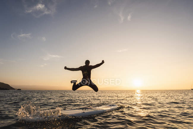 Young man jumping from paddleboard into water at sunset — Stock Photo
