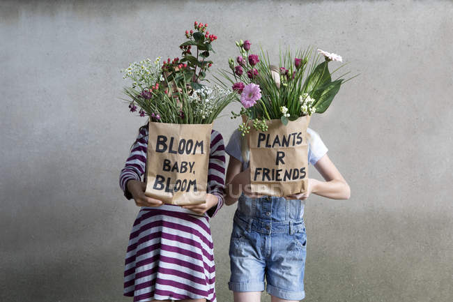 Two girls standing side by side hiding behind paper bags with flowers — Stock Photo