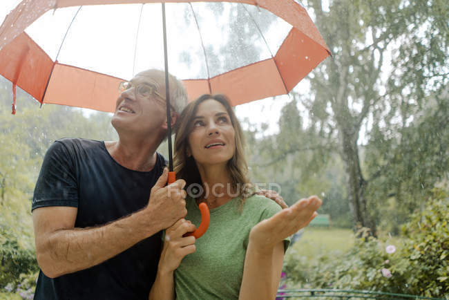 Sonriente pareja madura de pie en la lluvia bajo el paraguas — Stock Photo
