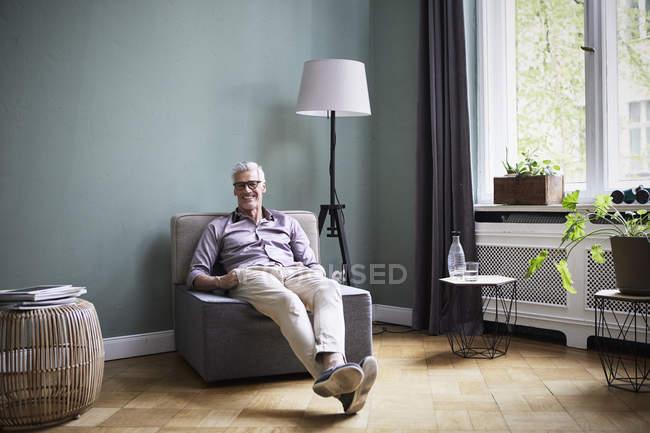 Retrato de hombre maduro sonriente sentado en el sillón en casa - foto de stock
