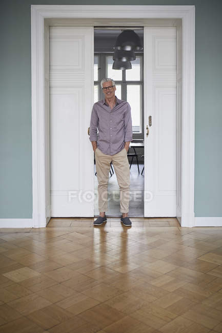 Portrait of confident mature man standing at home with hands in pockets — Stock Photo