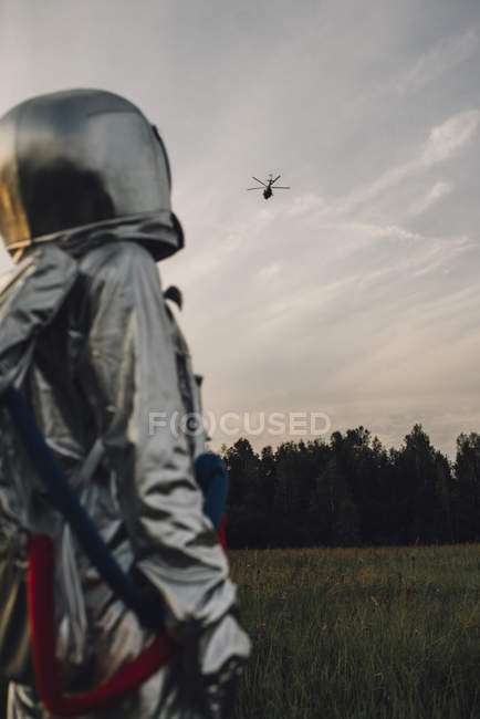 Spaceman exploring nature, watching helicopter in cloudy sky — Foto stock