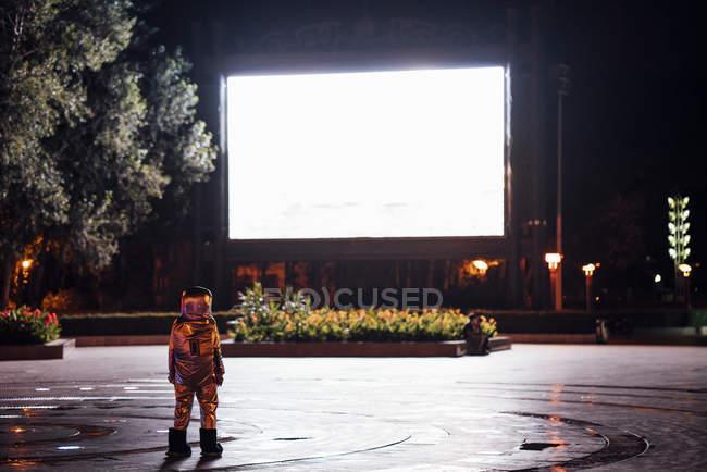 Spaceman de pie en la plaza por la noche atraído por la pantalla de proyección brillante - foto de stock