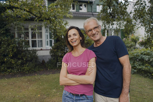 Happy mature couple standing in garden of house — Stock Photo