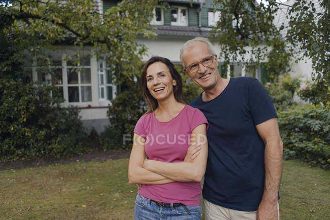 Felice coppia matura in piedi nel giardino di casa — Foto stock