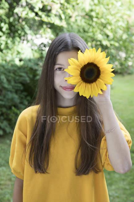 Портрет улыбающейся девушки с подсолнухом в саду — стоковое фото