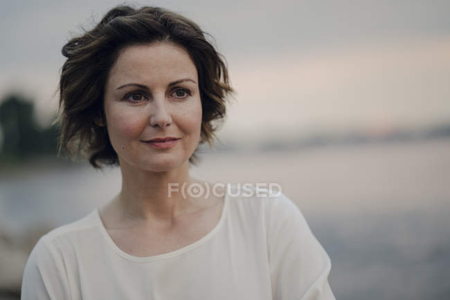 Thoughtful Caucasian Woman with short hair standing at river — Stock Photo