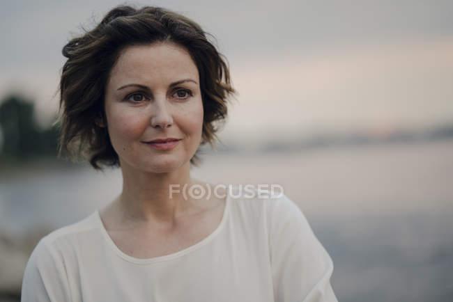 Pensativa mujer caucásica con el pelo corto de pie en el río - foto de stock