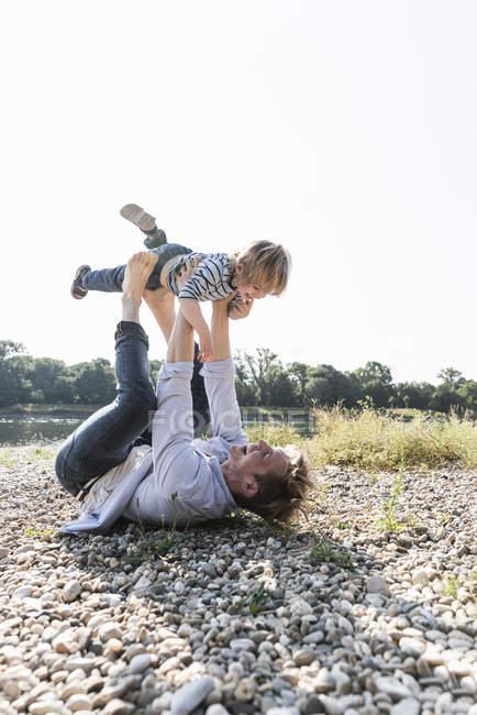Vater und Sohn mit Spaß am Flussufer, spielen Flugzeug — Stockfoto