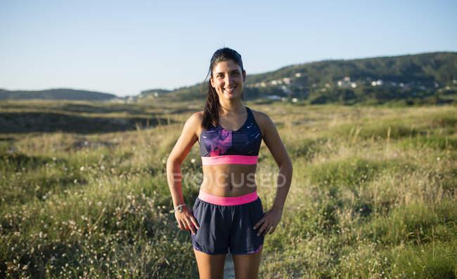 Портрет улыбающейся бегуньи, стоящей на лугу — стоковое фото