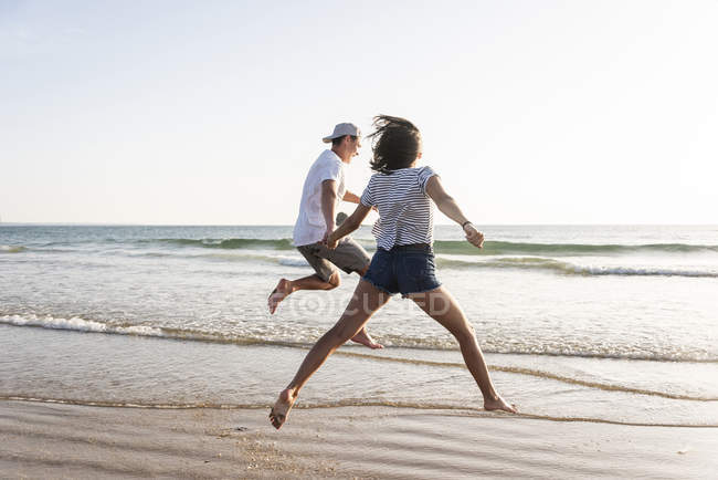 Young couple having fun on beach, running and jumping in sea — Foto stock