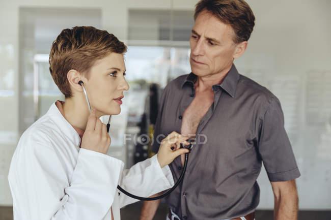 Врач-женщина осматривает пациента с помощью стетоскопа — стоковое фото