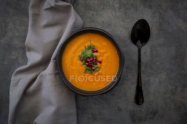 Bowl of carrot ginger coconut soup with topping of parsley and pomegranate seeds — Stock Photo
