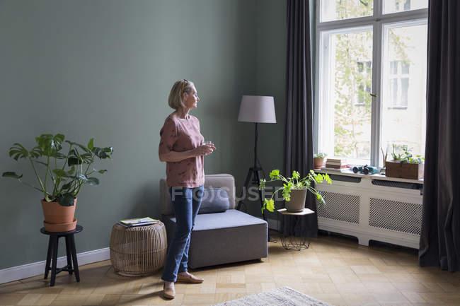 Зріла жінка в будинку, що дивиться з вікна — стокове фото