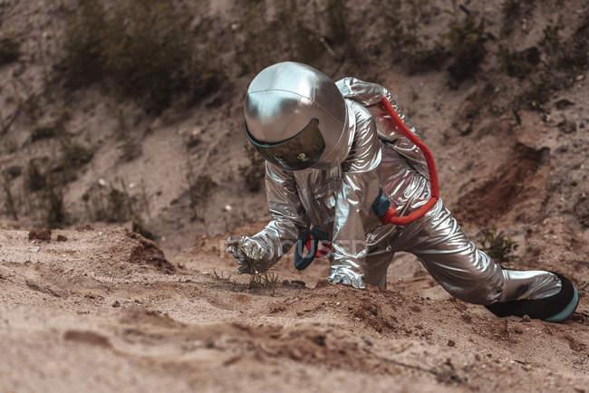Spaceman explorant une planète sans nom, examinant des plantes poussant sur une falaise — Photo de stock