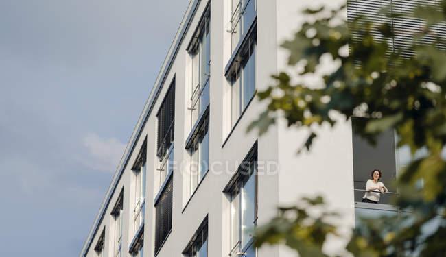 Donna che guarda fuori dalla finestra dell'ufficio di costruzione — Foto stock