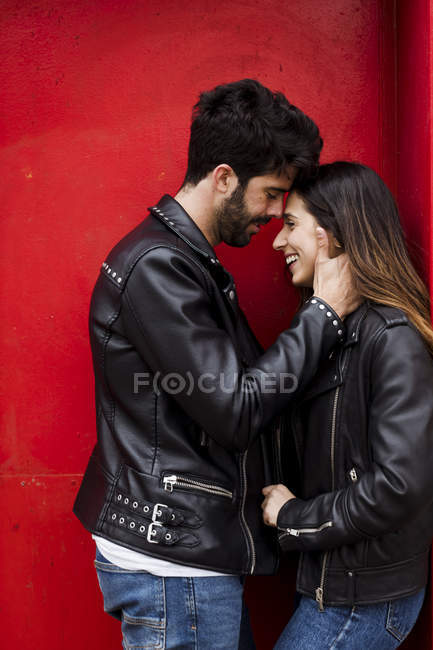 Счастливая молодая пара стоит у красной двери и смотрит друг на друга — стоковое фото