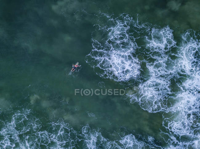 Indonesia, Bali, Aerial view of Dreamland beach, usrfer in the ocean — Stock Photo
