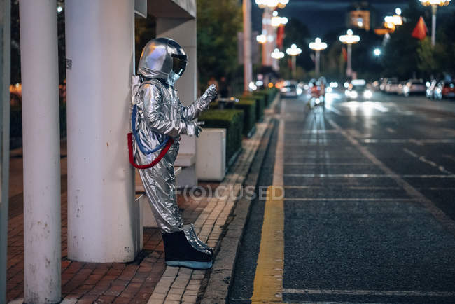 Spaceman standing at bus stop at night and holding cell phone — Stock Photo
