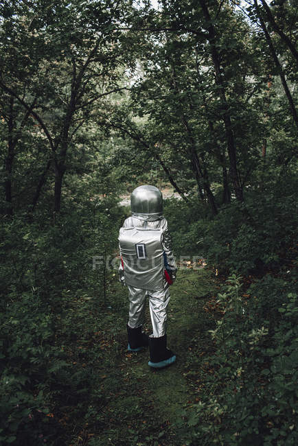 Spaceman exploring nature, walking in forest — Stock Photo