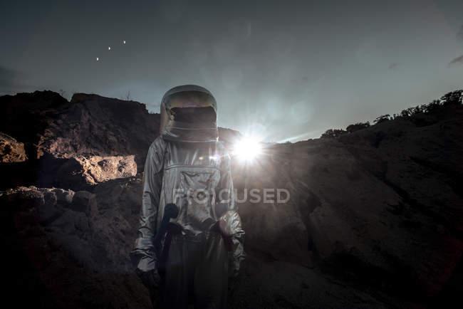 Spaceman exploring nameless planet at night — Stock Photo