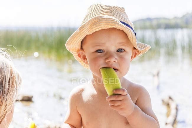Baby boy eating melon at lake — Stock Photo