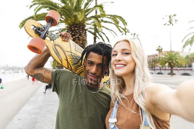 Испания, Барселона, портрет мультикультурной молодой пары, делающей селфи на набережной — стоковое фото