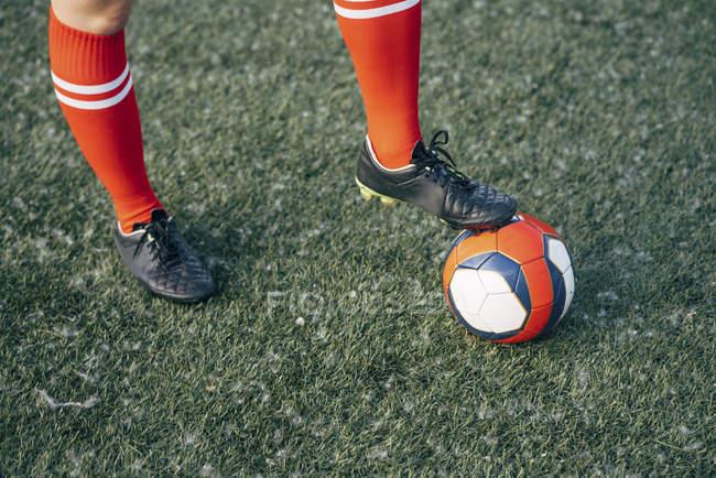 Ніжки жінки стояли на футбольному грунті з м'ячем — стокове фото
