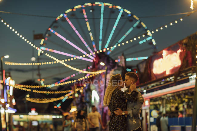 Happy young couple embracing and kissing at a funfair — Stock Photo