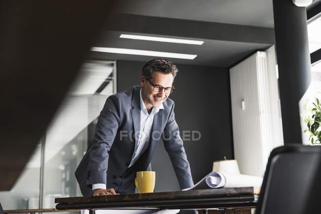 Homme d'affaires souriant dans le bureau regardant le plan sur le bureau — Photo de stock