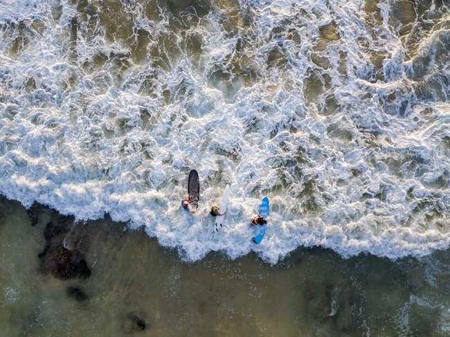 Indonesia, Bali, Aerial view of Dreamland beach, three surfers from above — Stock Photo