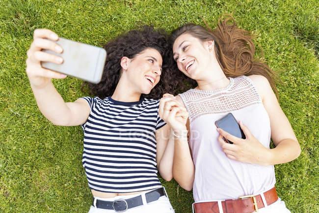 Deux amies heureuses allongées sur l'herbe prenant un selfie — Photo de stock