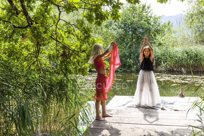 Two girls standing on jetty at a pond in fancy dresses — Stockfoto